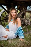 Beautiful boho girl with jeans jacket and white dress near trailer Royalty Free Stock Image
