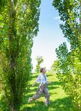 Beautiful boho style girl enjoying the freedom on a sunny day. Cheerful woman jumping on a green grass stock image