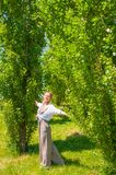 Beautiful boho style woman in fashionable jumpsuit enjoying summer time in park royalty free stock photography