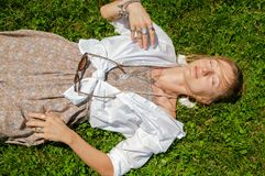 Beautiful boho style woman with a lot of accessories is lying on grass. Happy mometn and summer concept stock photography