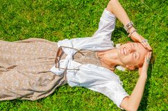 Beautiful boho style woman with a lot of accessories is lying on green grass. Happy mometn royalty free stock image