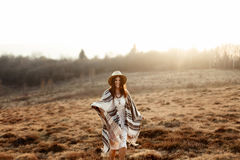 Beautiful boho woman hipster, smiling and standing at sunset in Royalty Free Stock Images