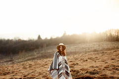 Beautiful boho woman hipster, smiling and standing at sunset in. Mountains, wearing hat and poncho, space for text stock photo