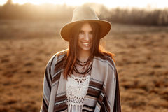 Beautiful boho woman hipster, smiling, wearing hat and poncho at. Sunset in mountains, true emotions, space for text stock photography
