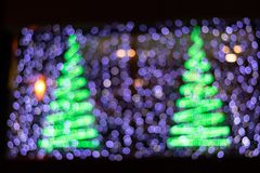Beautiful Bokeh background of two Christmas trees and purple lights royalty free stock photos