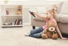Beautiful bored little girl watching tv. Bored little girl watching tv at home. Female kid sitting on floor carpet with her toy friend teddy bear, holding remote Royalty Free Stock Photos