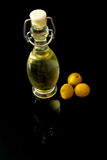 Beautiful bottle of olive oil and olives with reflection from the bottom isolated on a black. Background Royalty Free Stock Photo