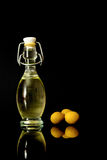 Beautiful bottle of olive oil and olives with reflection from the bottom isolated on a black. Background Stock Photo