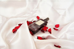 A beautiful bottle of perfume on the background of silk. Fashion & Style. Royalty Free Stock Photo