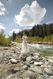 Beautiful boudoir sexy Bride in bathrobe dress. young girl fashion Stylish with bouquet on the nordic Karelian nature. Landscape background forest Waterfall Royalty Free Stock Photography