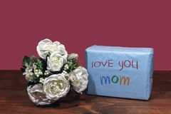 Beautiful bouquet of arranged flowers and a present with a message `Love You Mom` on a wooden table. royalty free stock image