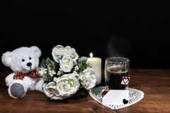 Beautiful bouquet of arranged flowers white candle on a holder, a hot glass of tea on a wooden table. royalty free stock image
