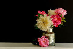 Beautiful bouquet with artificial silk flowers peonies in the can black background.  Royalty Free Stock Image