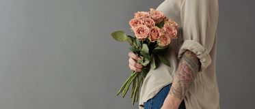 A beautiful bouquet of beige roses cappuccino. The woman is holding flowers in her hand tatoo on a gray background. Mother`s Day, Valentine`s Day stock images