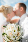 Beautiful bouquet of the bride executed from light beige roses with the wedding kissing couple Royalty Free Stock Photo