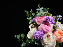 Beautiful bouquet of bright white pink purple roses flowers with. Green leafs on black background royalty free stock photo