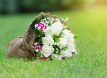 Beautiful bouquet of bright white rose flowers on green grass at Stock Photos