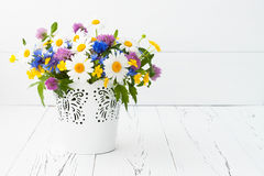 Beautiful bouquet of bright wildflowers in basket over old rustic table. Mothers day greeting card concept. Royalty Free Stock Image