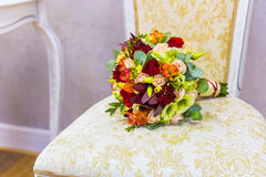 Beautiful bouquet of colorful flowers and green roses lying on a chair close-up Stock Image