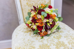 Beautiful bouquet of colorful flowers and green roses lying on a chair close-up Royalty Free Stock Photography