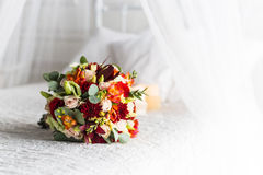 Beautiful bouquet of colorful flowers and green roses lying on a chair close-up Stock Images
