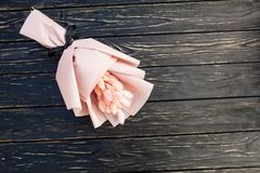 Beautiful bouquet of dry pink flowers on a wooden black background. Minimalism, space for text. Gift Card. Abstract spring theme royalty free stock image