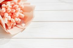 Beautiful bouquet of dry pink flowers on a wooden white background. Minimalism, space for text. Gift Card. Abstract spring theme royalty free stock image