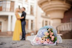 Beautiful bouquet of flowers on the cobbled road. Against the blurred background of loving hugging couple Stock Image