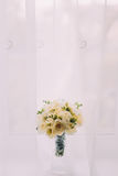Beautiful bouquet of flowers in cut glass vase on windowsill. Bright window with white curtains at background Stock Photos