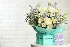 Beautiful bouquet of flowers and gift box on table against light background. Space for text stock photo