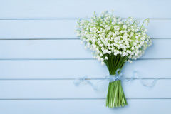 Beautiful bouquet of flowers lily of the valley on  blue wooden table from above. Stock Photo