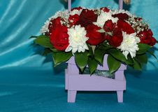 A beautiful bouquet of flowers from roses and chrysanthemums in. A decorative basket on a blue background. Macro. You can use it as the background Stock Photo