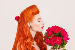 Beautiful bouquet of flowers. Valentines day concept. Retro girl with red lips in studio. Valentines day beauty redhead model with Stock Images