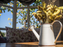 Beautiful bouquet flowers in watering can on wooden table and bl Stock Images