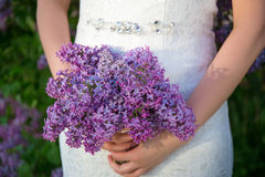 Beautiful bouquet of lilac flowers in bride's hands Royalty Free Stock Image