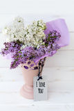 Beautiful bouquet of lilac with i love you message card. Bouquet of purple and white lilac on a white wooden background with i love you label card royalty free stock photo