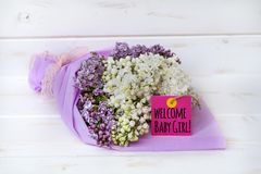 Beautiful bouquet of  lilac with  welcome baby girl card. Bouquet of purple and white lilac on a white wooden background with pink welcome baby girl  message Stock Image