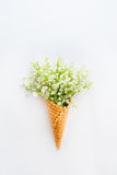 Beautiful bouquet of lilies of the valley,may-lily flowers in a waffle corn on the white background, top view. Selective focus. Sp Royalty Free Stock Image