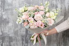 Beautiful luxury bouquet of mixed flowers in woman hand. the work of the florist at a flower shop. Beautiful bouquet of mixed flowers into a vase on wooden table stock photo