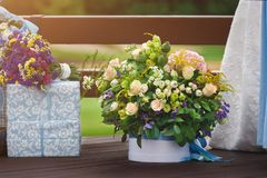 Beautiful bouquet next to wedding gifts outdoors. Beautiful bouquet next to wedding gifts on bench outdoors stock image