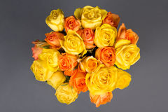 Beautiful bouquet of orange and yellow roses over grey Stock Photo