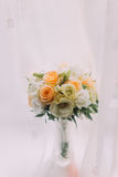 Beautiful bouquet of pale white orange roses in cut glass vase on windowsill. Bright window with white curtains at background Stock Photos