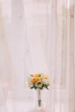 Beautiful bouquet of pale white and orange roses in cut glass vase on windowsill. Bright window with white curtains at background Royalty Free Stock Photo