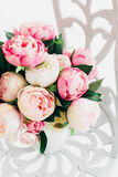 Beautiful bouquet peonies on forged vintage chair in white room Stock Photography
