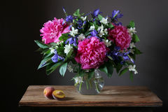 Beautiful bouquet of peonies, irises and Jasmine in the jar on t. Beautiful bouquet of peonies, irises and Jasmine in the jar. Still life with flowers in a vase Royalty Free Stock Images