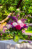 Beautiful bouquet of peonies and lupine on the table in the gree Stock Photo