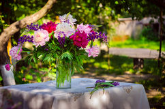 Beautiful bouquet of peonies and lupine on the table in the gree Stock Photography