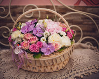 Beautiful bouquet of pink flowers in basket on decorated table Royalty Free Stock Photography