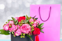 Beautiful bouquet of pink and red roses and red ribbon in a circ. Ular black box near pink gift bag. Valentines and anniversary concept Royalty Free Stock Image