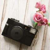 Beautiful bouquet of pink roses in blue vase, old photo camera on a wooden background.  Royalty Free Stock Photos